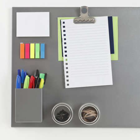 magnetic clip: Gray metalic magnetic board with blank piece of paper held by a magnetic clip