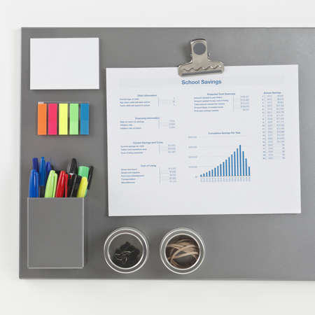 magnetic clip: Gray metalic magnetic board with a spreadsheet printout held by a magnetic clip