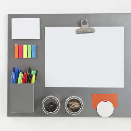 Gray metalic magnetic board with blank paper sheet held by a magnetic clip photo