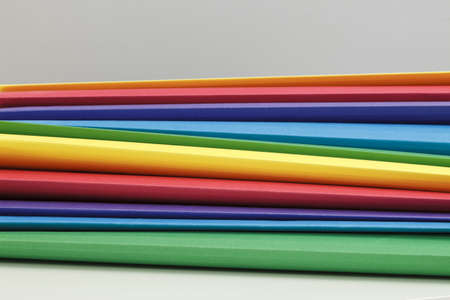 Stack of multicolor suspended folders on a white desk, gray wall Stock Photo