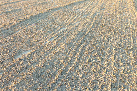 Waves and footprints on a sandy beach. Stock Photo
