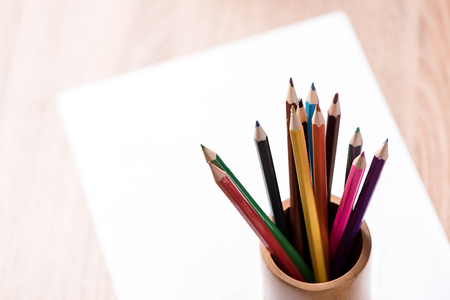 coloured pencil: coloured pencil and paper note on wood table