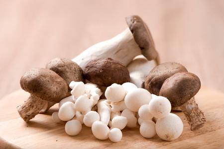 King oyster mushroom and shimeji mushroom and Shitake mushroom on chopping block ,wood table Foto de archivo