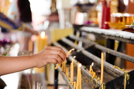 enlightening: woman hand lighting candles in a church Stock Photo