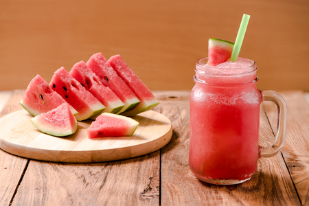 Refreshments: Closeup watermelon juice in glass on wood table with with slices of watermelon Stock Photo