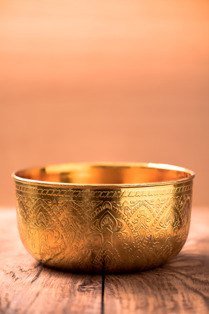 ancient yoga: Gold bowl on wood table Stock Photo