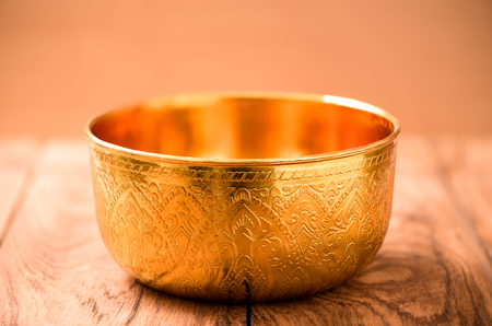 singing bowls: Gold bowl on wood table Stock Photo