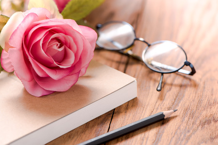 Diary with book note and pencil and glasses and rose on wood table,with vintage filter