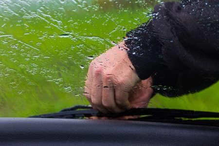 windscreen wiper: the man in the rain repairs a window wiper by car Stock Photo