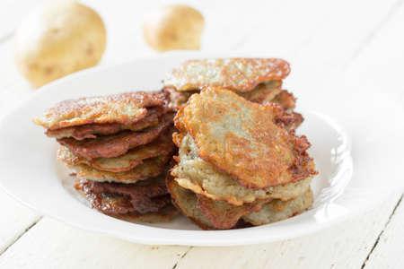 papas doradas: croquetas de patata con una corteza de oro en una placa de cerámica blanca y crudo patatas en una tabla