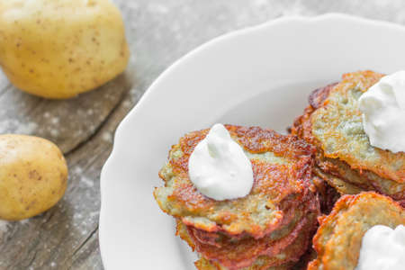 hash browns: patate fritte con una crosta dorata con panna acida in un piatto in ceramica bianca e una patata grezza sulla vecchia scheda scoppio grigio