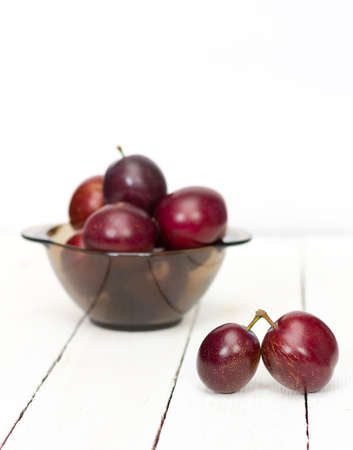 wares: big ripe plums in glass wares on white boards