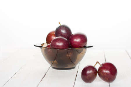 wares: big ripe plums in glass wares on a white background