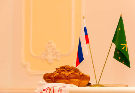 registrar: round loaf on the table and the flags of Russia and the Republic of Adygea