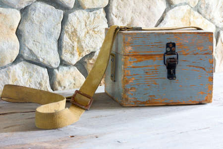 tarpaulin: old wooden case on a tarpaulin belt near a stone wall closeup Stock Photo