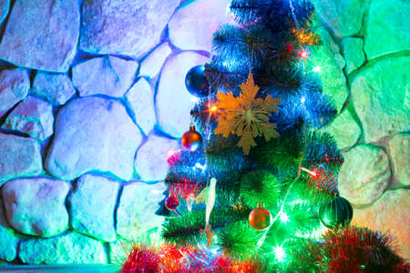 plastic christmas tree: Christmas lights and colorful toys on New Year tree on a background of a stone wall in the evening Stock Photo