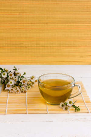 chamomile tea: strong brewed chamomile tea in a transparent glass bowl on a bamboo mat on an old white wooden table surrounded by fresh camomile flowers on bamboo background wallpaper