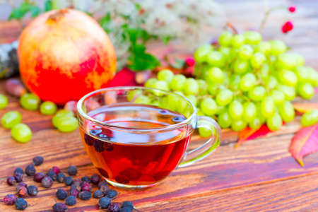 wei�e trauben: infusion of hawthorn fruit on the background of white grapes, pomegranates and autumn leaves, selective focus Lizenzfreie Bilder