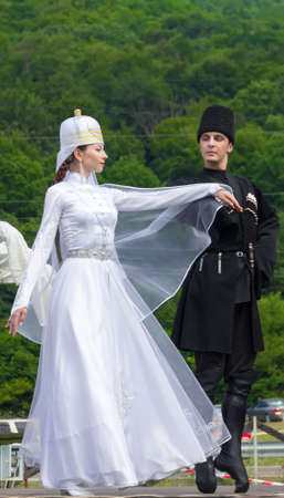 jungle girl: Adygea, RUSSIA - JULY 25 2015: Young guy with a girl in Adyghe national costumes dancing traditional dance at an ethnofestival in the Foothills of Caucasus in Adygea Editorial