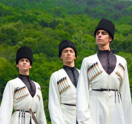 ethnic dress: Adygea, RUSSIA - JULY 25 2015: Young guys in Adyghe national costumes dancing traditional dance at an ethnofestival in the Foothills of Caucasus in Adygea
