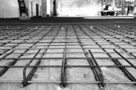 channeled: the reinforcing grid fastened with a wire from a channeled steel rod under filling of concrete floors, in black and white Stock Photo