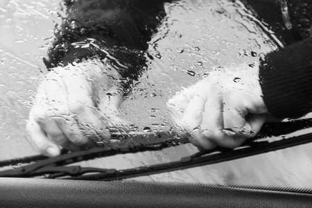 the man in the rain repairs a window wiper by car in black and white