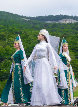 ethnic festival: Adygea, RUSSIA - JULY 25 2015: Female dancers in traditional costumes Circassian green hills in the background. Ethnic festival in the foothills of the Western Caucasus in Adygea