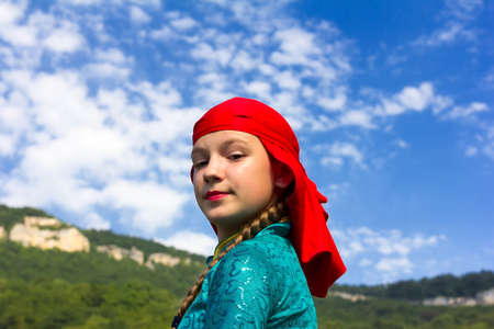 ethnic festival: Adygea, RUSSIA - JULY 25 2015: Portrait of a young dancer in traditional Circassian dress on a background of sky and mountains. Ethnic festival in the foothills of the Western Caucasus in Adygea Editorial