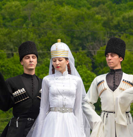 ethnic dress: Adygea, RUSSIA - JULY 25 2015: Young guys and girl dancers in traditional Adyghe dresses, dance at an ethnofestival in the Foothills of the Western Caucasus in Adygea Editorial