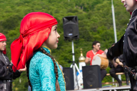ethnic festival: Adygea, RUSSIA - JULY 25 2015: Portrait of a young dancer in traditional Indian dress on the background of the scene, the temple and the green hill. Ethnic festival in the foothills of the Western Caucasus in Adygea