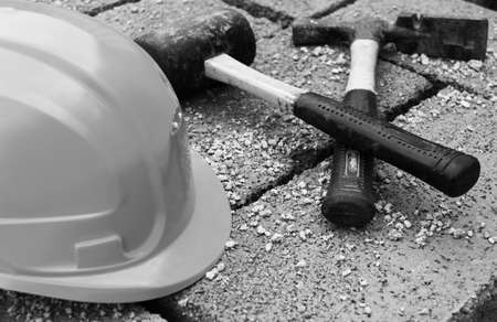concrete blocks: an orange protective helmet and old  hammers on gray concrete blocks closeupt, in black and white photo
