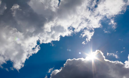 in the sky the sun breaks through the clouds Stock Photo