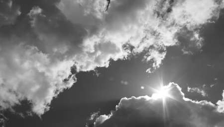 black and white: in the sky the sun breaks through the clouds. Black and white photo