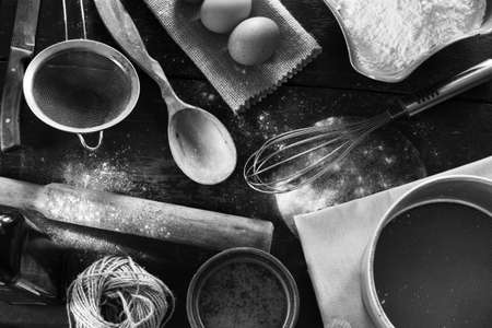 old items: A set of old kitchen items close-up view from above. Kitchen table in a rustic style. Products for baking flour, eggs, salt. Black and white photo Stock Photo