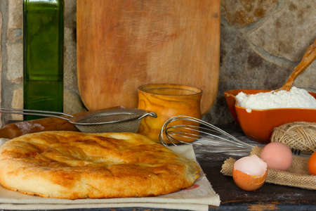 italian bread: Traditional Italian bread, focaccia, broken egg with the yolk, whole eggs on the background of a stone wall with utensils. Rustic style. Side view close-up. Selective focus.