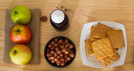 productos naturales: Las manzanas, avellanas, galletas y mermelada de arándanos con malvaviscos para el desayuno. Productos naturales para el postre. Foto de archivo