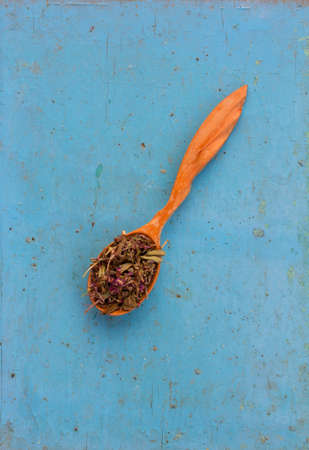 healthful: Dried herbs (Salvia officinalis) in a wooden spoon on the old blue background. Ingredient for cooking healthful beverage. The concept of rustic herbal therapy. Ingredient for cooking healthful beverage.