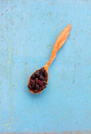 healthful: Dried rose hips in a wooden spoon on the old blue background. Ingredient for cooking healthful beverage. The concept of rustic herbal therapy. Ingredient for cooking healthful beverage. Stock Photo