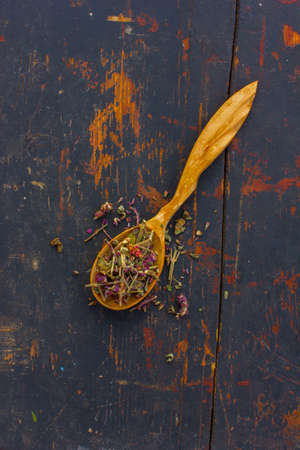 healthful: Dried herbs (Salvia officinalis) in a wooden spoon on the old cracked black background. Ingredient for cooking healthful beverage. The concept of rustic herbal therapy. Ingredient for cooking healthful beverage.