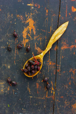healthful: Dried rose hips in a wooden spoon on the old black background. Ingredient for cooking healthful beverage. The concept of rustic herbal therapy. Ingredient for cooking healthful beverage. Stock Photo