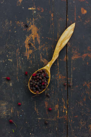 healthful: Dried hawthorn berries in a wooden spoon on the old cracked black table. Ingredient for cooking healthful beverage. The concept of rustic herbal therapy