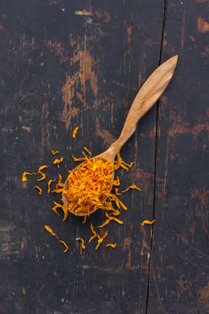 healthful: Dried yellow petals Jerusalem artichoke in a wooden spoon on the old cracked black table. Ingredient for cooking healthful beverage. The concept of rustic herbal therapy Stock Photo