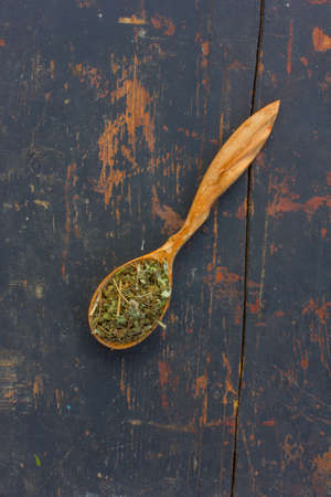 healthful: Dried herbs in a wooden spoon on the old cracked black background. Ingredient for cooking healthful beverage. The concept of rustic herbal therapy