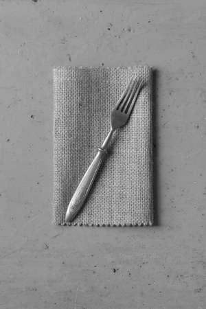 grunge flatware: Old vintage fork on a linen napkin on a grey background. Top view