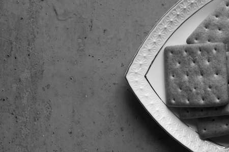 free dish: Part of a square white ceramic dish with cookies and crackers on an old stained background closeup. Selective focus. Black and white photo. Free space for text. Copy space. Top view
