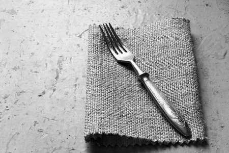 grunge silverware: Old vintage fork on a linen napkin on a grey background. Top view