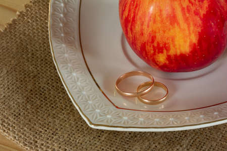 matting: Male and female gold wedding rings and red ripe Apple in a white ceramic saucer on the matting. Closeup top view. Rustic style. Selective focus