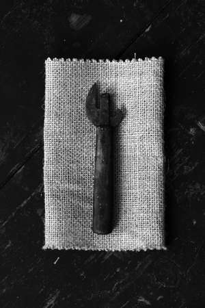 can opener: Old dirty can opener on the matting, on black boards. Top view closeup. Rustic styleThe concept of rustic kitchen. Black and white photo