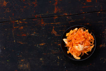 korean salad: Korean salad made of grated carrots with red fish and onions marinated in the old black cracked background. Copy space. Free space for text, Close-up, top view