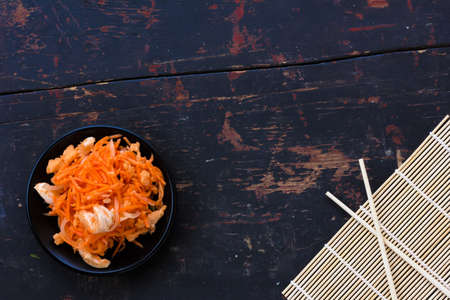 korean salad: Korean salad made of grated carrots with red onions and fish sauce and chopsticks on the old black cracked background, Close-up, top view